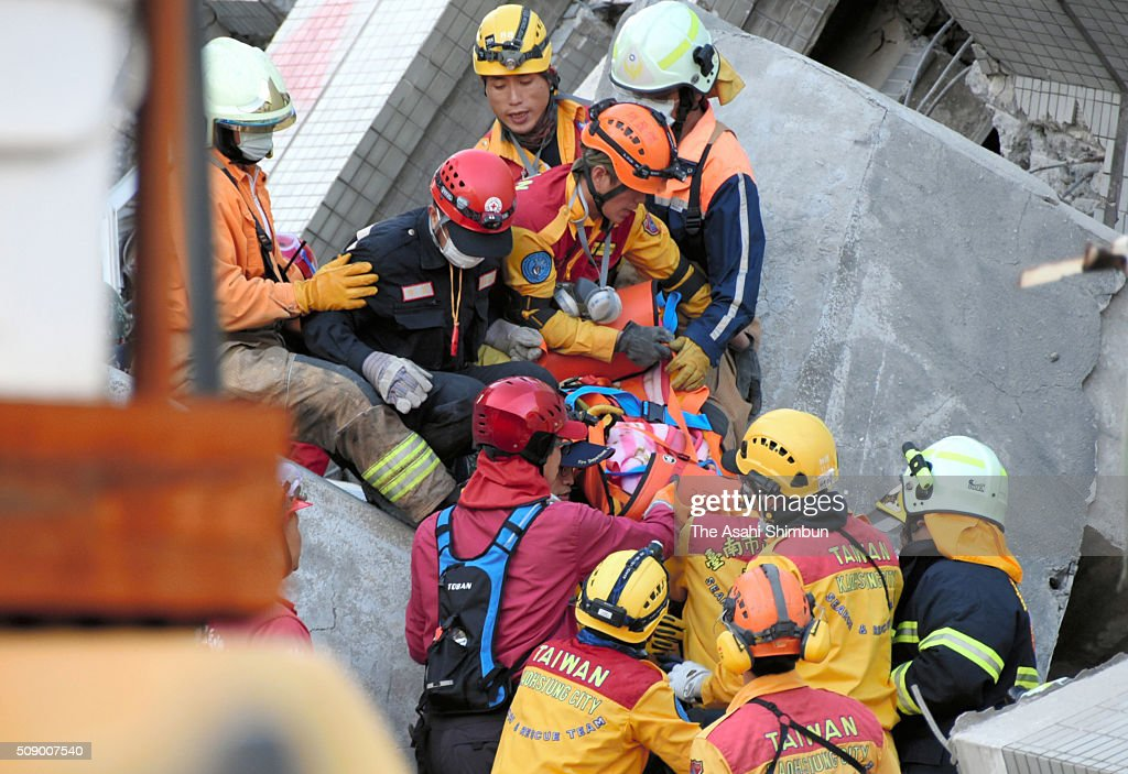 A 8-year-old girl (C) is carried by rescue workers at a collapsed building 61 hours after the magnitude 6.4 earthquake jolted on Saturday on February 8, 2016 in Tainan, Taiwan. The crucial 72-hour approaching, more than 100 people are believed to be trapped in the building.