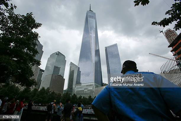 A 9/11Security worker keeps an eye on tourist as he patrols around Ground Zero and One World Trade Center on July 4 2015 in New York City Security...