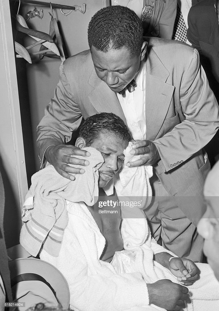 9/12/51New York NY One of Sugar Ray Robinson's handlers wipes off the sweat and blood from the boxer's face in the dressing room after the 31yearold...