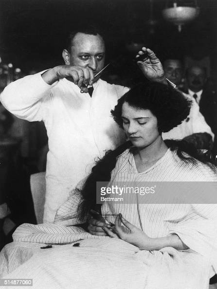 Miss Muriel Redd of Chicago appearing in show 'Tickle Me' having her hair bobbed by Barber Lewis Morgan Mgr at the Hotel McAlpin Barber Shop