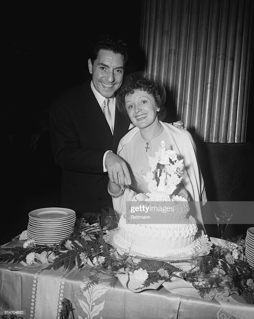 French singer Edith Piaf about to cut the wedding cake with her husband, Jacques Peals, during the Versailes night club wedding reception that followed their wedding reception that folowed their marriage, Sept. 20. They were wed at the St. Vincent De Paul Roman Catholic Church in a ceremony conducted in French. Actress Marlene Dietrich was a Matron of Honor.