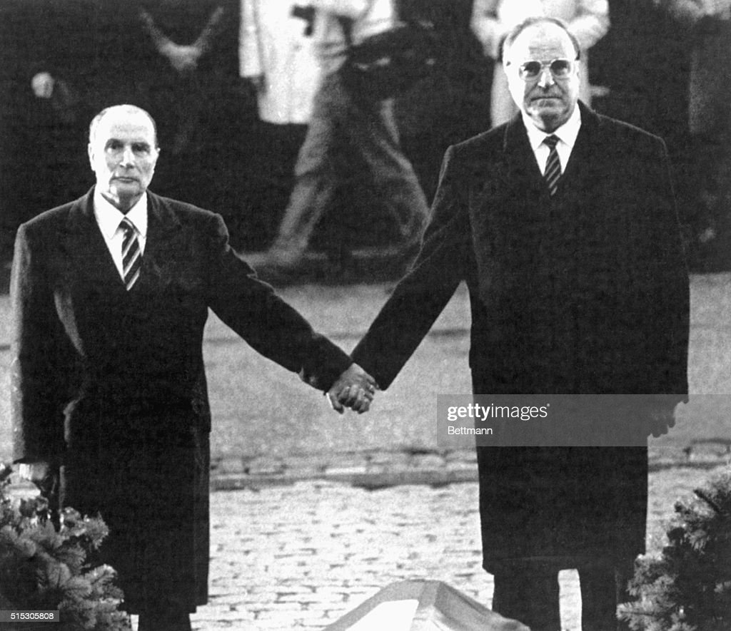 Verdun, France- French President <a gi-track='captionPersonalityLinkClicked' href=/galleries/search?phrase=Francois+Mitterrand&family=editorial&specificpeople=208938 ng-click='$event.stopPropagation()'>Francois Mitterrand</a> (L) and West German Chancellor <a gi-track='captionPersonalityLinkClicked' href=/galleries/search?phrase=Helmut+Kohl&family=editorial&specificpeople=202518 ng-click='$event.stopPropagation()'>Helmut Kohl</a> hold hands while the national anthems of both countries are played by a military band, during a ceremony commemorating the victims of World War II.