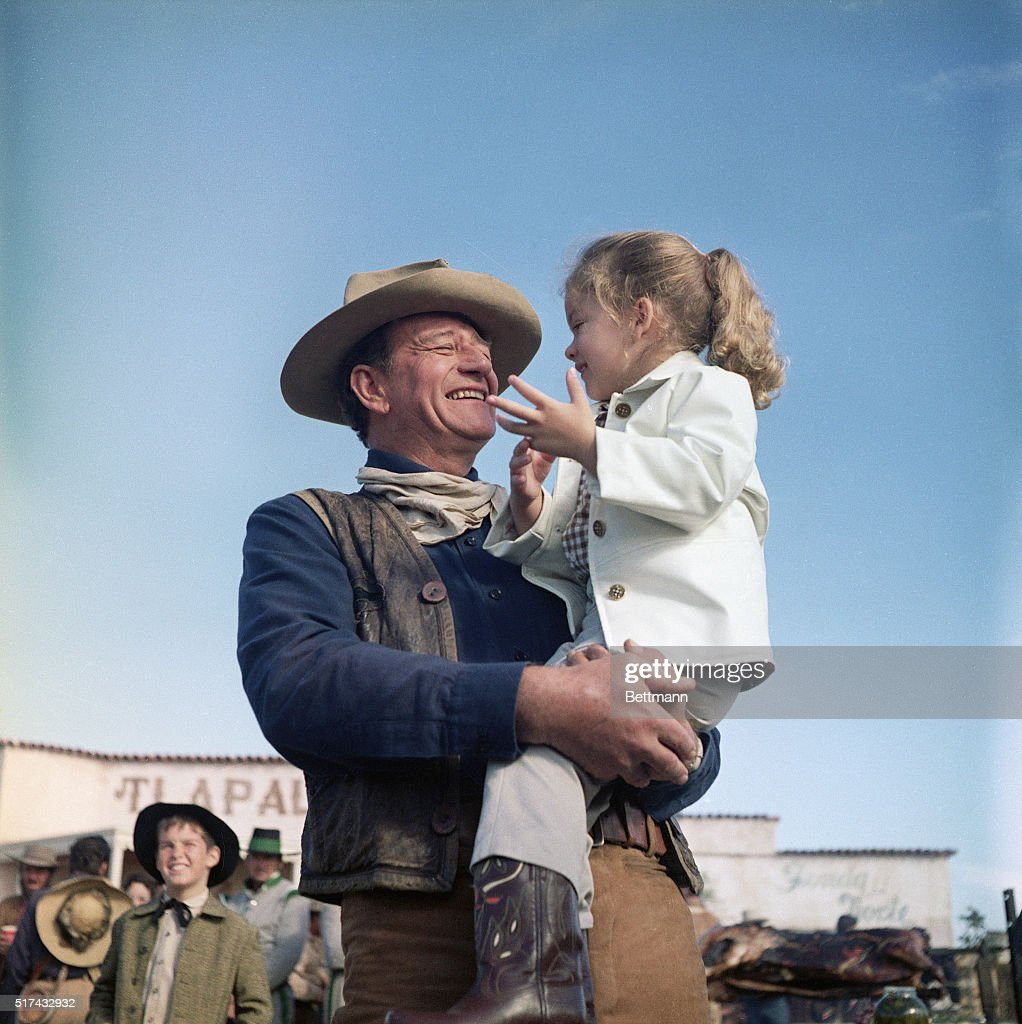 John Wayne holds his daughter, Aissa, on the set of 'The Alamo.'