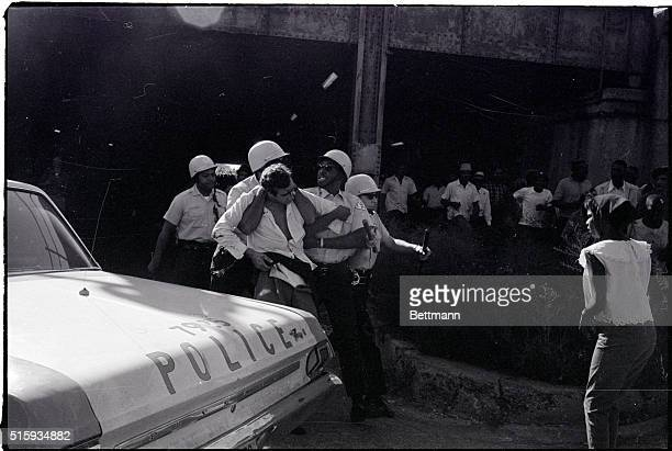 9/4/1966Cicero IL A heckler with blood streaming from a hit on the head and about to lose his pants is held in an iron grip by a policeman after his...
