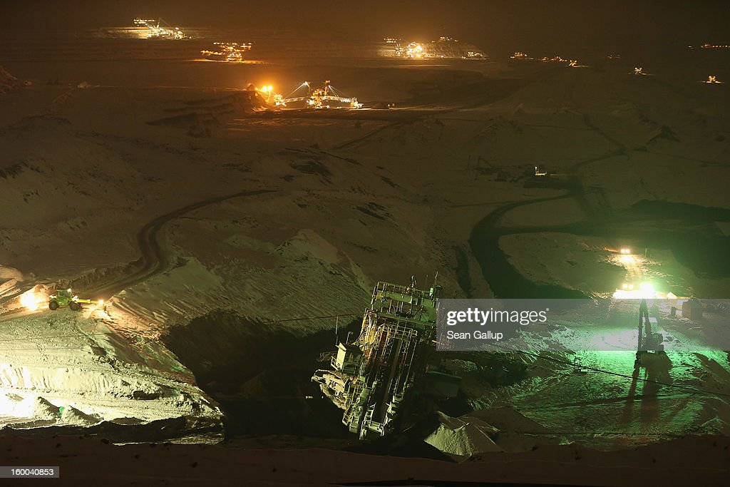 A 950-tonne bucket excavator stands on its treads after workers set it upright over the course of several hours following an accident at an open-pit coal mine as other ecavators stand illuminated behind on January 25, 2013 near Deutzen, Germany. The bucket excavator tipped over last summer after plateaus of earth and sand nearby gave way, pushing a layer of coal underneath. The excavator had been lying severaly tilted to one side ever since at the Vereinigtes Schleenhain mine, which is operated by Mibrag. Open-pit lignite coal mines are still common across eastern Germany and produce coal for local electricity production.