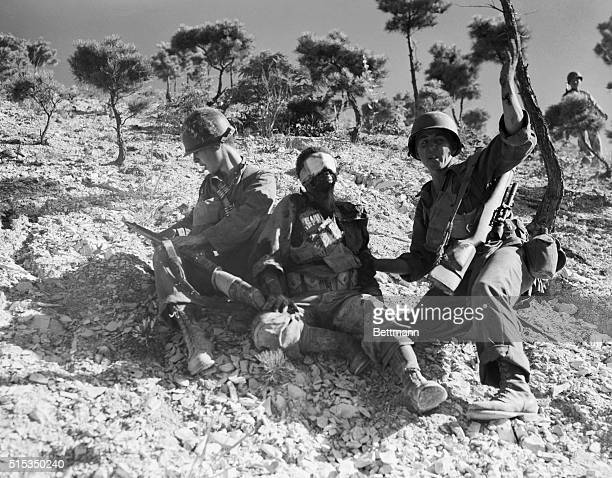 A US soldier waves frantically for medics to come assist a fallen comrade who took a mortar blast in the face during fighting in the Pohang front...