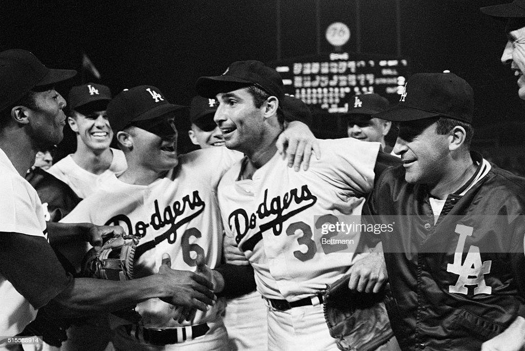 Dodger pitcher Sandy Koufax (#32) is mobbed by teammates on the field after pitching a perfect game. Shown in the picture are (L to R): Willie Davis, Wes Parker, Ron Fairly, Sandy Koufax, and Don LeJohn.