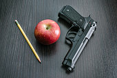 9mm Beretta 92FS type handgun with apple and pencil depicting the question whether to arm teachers in the classroom to defend students against active shooters.