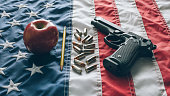 9mm Beretta 92FS type handgun with apple and pencil and ammunition over the USA Flag depicting the question whether to arm teachers in the classroom to defend students against active shooters.