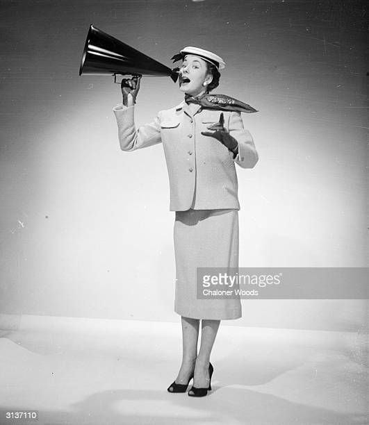 A woman modelling a suit from Harrods department store in London and shouting for help using a handheld megaphone