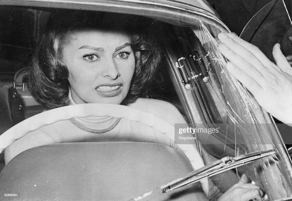 Italian film star Sophia Loren cowers in her car as a crowd of ardent fans press around her smashing the windscreen in their eagerness to see her...