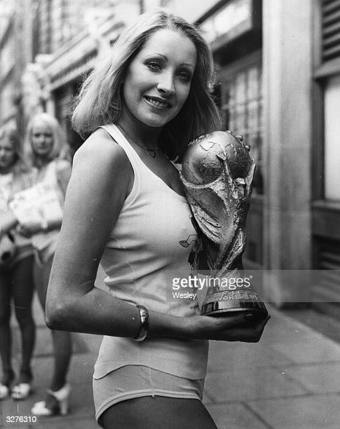 A model dressed in World Cup football gear holds a replica of the FIFA World Cup Trophy used to replace the original gold cup valued at 17000