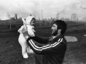 Desmond Robbins holding his baby on waste ground with an industrial background and smoking chimneys