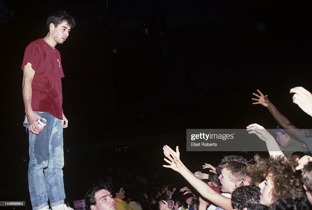 MCA from American hip hop group Beastie Boys sprays the contents of a can of Budweiser beer over members of the audience from the stage at the...