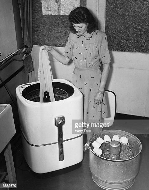 A woman taking washing out of a new British machine before replacing it with a receptacle holding the dirty dishes The new Thor washing machine can...