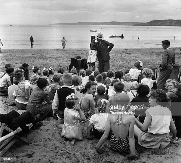 Ventriloquist Tom King entertaining children with his act on the beach at Scarborough Yorkshire Original Publication Picture Post 5997 A Trip To...