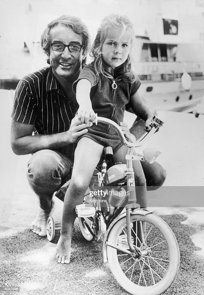 British actor and comedian Peter Sellers (1925 - 1980) takes his daughter Victoria out on her miniature motorbike, during a holiday in Monte Carlo.