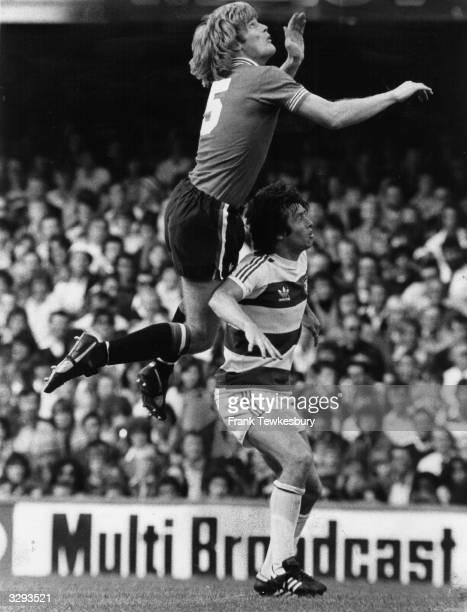 Footballer Gordon McQueen beats Peter Eastoe of Queens Park Rangers to a high ball at Loftus Road