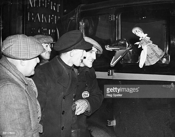 London taxidrivers watch a puppet show put on by colleague Charles Tebbutt in the theatre he made in his black cab