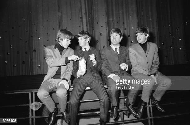 Pop group The Beatles from left to right George Harrison Ringo Starr John Lennon and Paul McCartney eating a bag of popcorn during a photocall at...