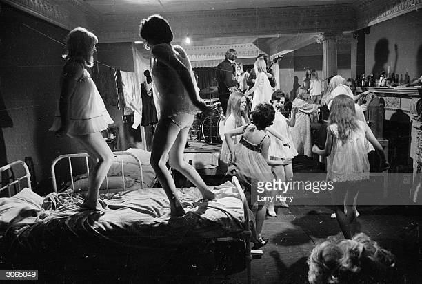 Pupils from St Trinian's allgirl school go wild at a pyjama party in their school dormitory