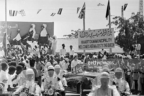 Queen Elizabeth II and President Dr El Tieani El Mahi drive past a sign welcoming her to the municipality of Khartoum during a royal tour of the...