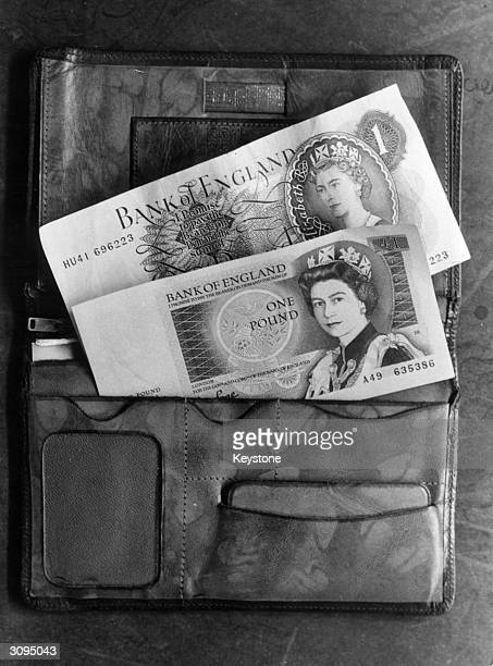 A closeup of two pound notes in a wallet The smaller one issued today by the Bank of England features the same portrait of Queen Elizabeth II that...