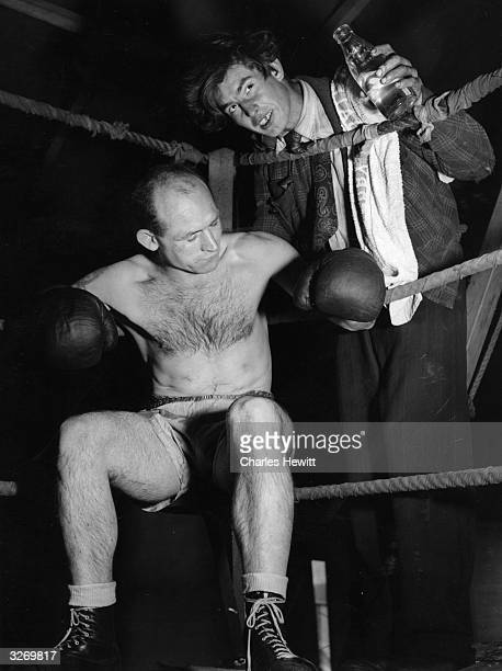 A fairground boxer receives water from his second as he waits in his corner for a challenge from the audience at Newbury Fair Original Publication...
