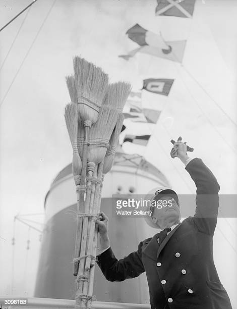 An officer of the SS United States with the brooms which will be hoisted on the mast of the ship on its arrival in New York