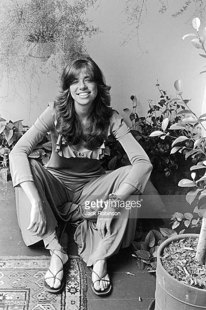 Portrait of American singer Carly Simon smiling and sitting on the floor among potted plants New York City