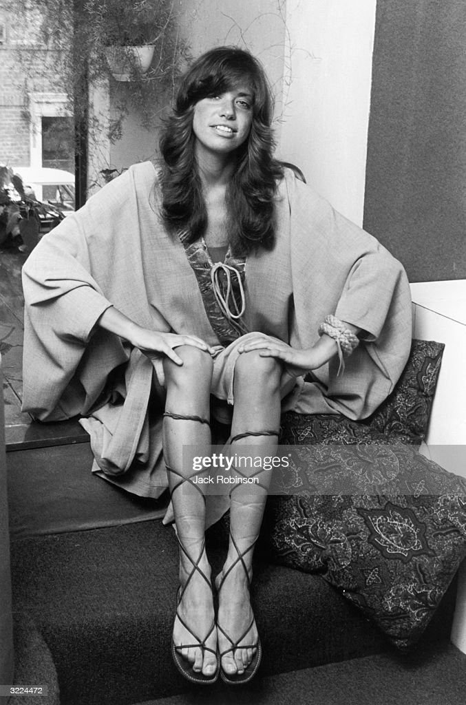 Portrait of American singer Carly Simon smiling sitting on steps with her hands on her knees and wearing a robe and kneehigh Roman sandals New York...