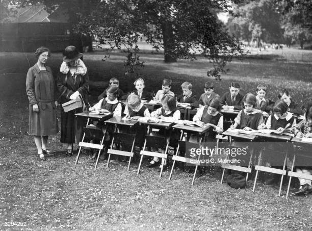 Children from various London schools are being taught in St James's Park by the LCC and the Honorable Mrs Grenfell is viewed inspecting their work