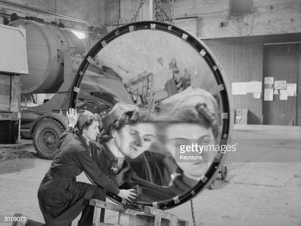 Mrs Kathleen Would catches a warped reflection of herself as she polishes one of the giant reflectors at a searchlight factory in the Midlands during...