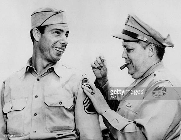 Sergeant Joseph P DiMaggio former New York Yankees baseball player smiles as Brigadier General William J Flood attaches a new 7th AAF shoulder patch...