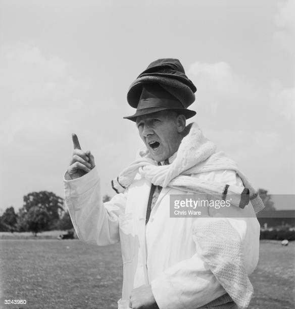 Umpire Arthur Belson wears several hats and sweaters at once during a cricket match at Amersham Hill Customarily the umpire will hand the bowler his...