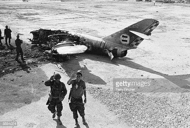 Advancing Israeli troops pass the wreckage of an Arab warplane near El Arish Airport during the SixDay war