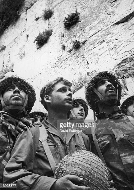 Several Israeli soldiers standing close together in front of the Western or Wailing Wall in the old city of Jerusalem following its recapture from...