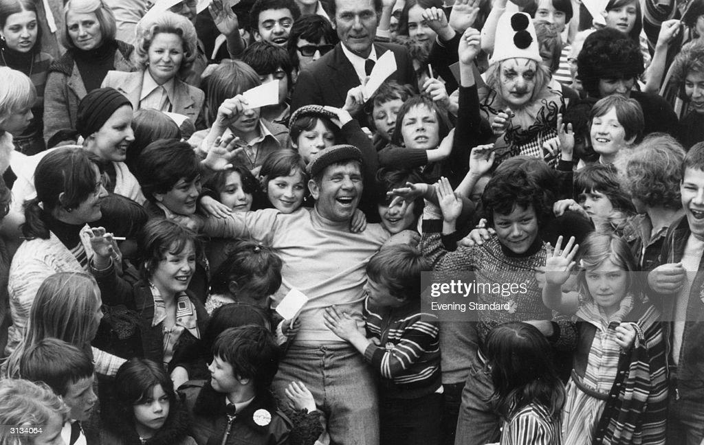 English comic actor Norman Wisdom amidst a crowd of young fans in Finsbury Park, London.