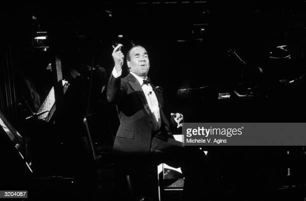 American singer and cabaret artist Bobby Short raises his hand in the air while seated at a piano during a 100th birthday celebration for the late...