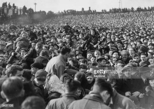 Women and children being passed over the heads of the crowd during the crush in which 33 football fans died during a FA Cup match between Stoke and...