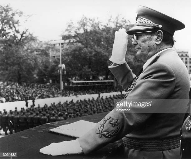 Yugoslav statesman and president Marshal Tito salutes as troops march past at a military parade at Belgrade to mark the 30th anniversary of liberation