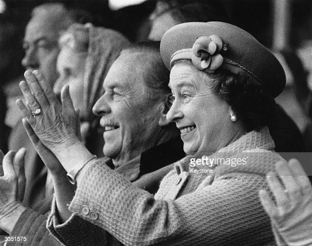 Queen Elizabeth II applauds enthusiastically as her husband Prince Philip the Duke of Edinburgh tackles the obstacle course for coaches at the Royal...