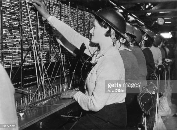 Women operators at a London telephone exchange wearing helmets during an airraid alert