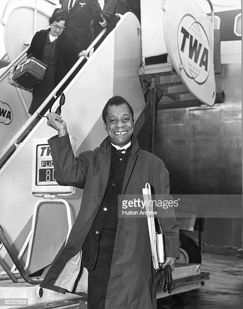 Author and playwright James Baldwin stands with his arm raised in the air holding up a pair of sunglasses on a tarmac in front of a TWA airplane...