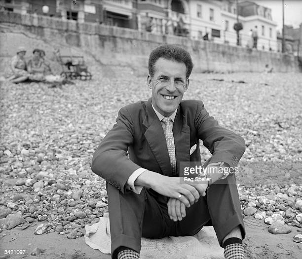 British entertainer and television presenter Bruce Forsyth sitting on a beach