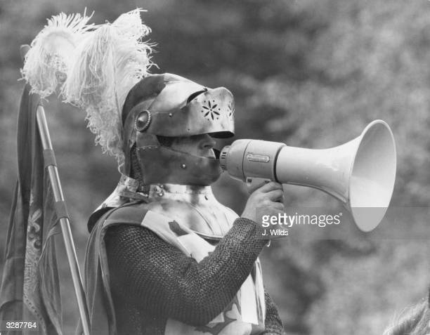 A man dressed as a knight in armour uses a loudhailer to direct operations at a rehearsal for the medieval jousting tournament being held to...