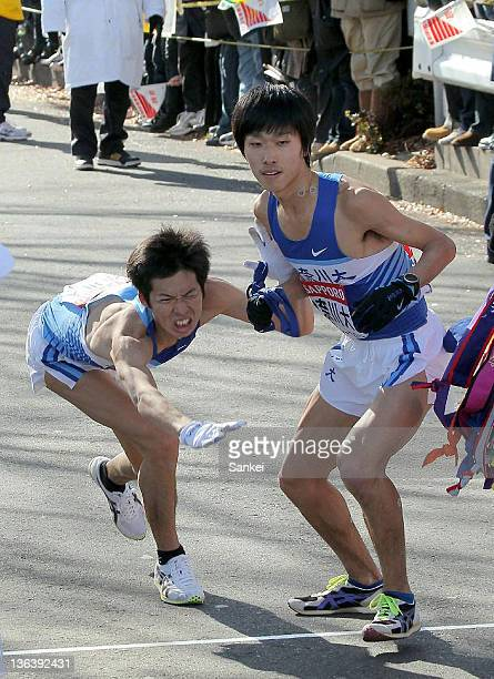 9th runner of Kanagawa University Shun Suzuki manages to pass the sash to Toshimitsu Takahashi during the 88th Hakone Ekiden on January 3 2012 in...