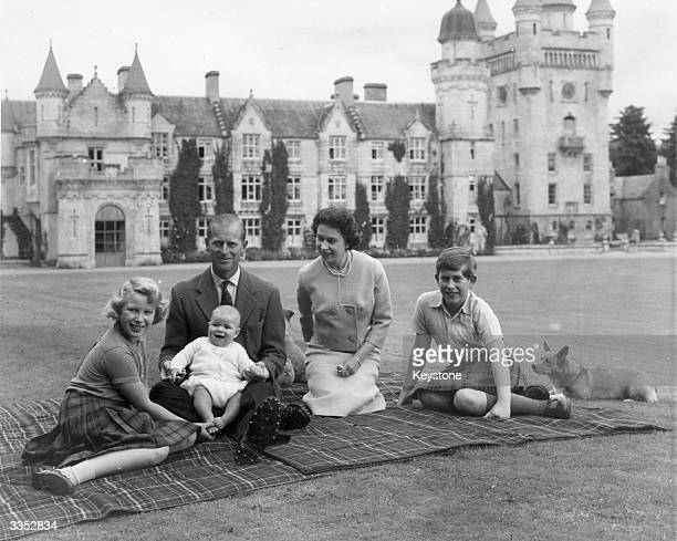 Queen Elizabeth II and Prince Philip Duke of Edinburgh with their children Prince Andrew Princess Anne and Charles Prince of Wales sitting on a...