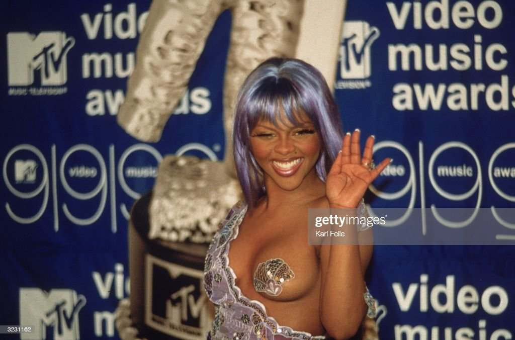 Rap artist Lil' Kim, wearing a revealing, purple-sequined dress with pasties, waves to the camera at the MTV Video Music Awards at the Metropolitan Opera House at Lincoln Center, New York City.
