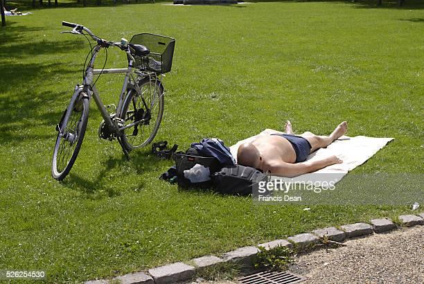 DENMARK / COPENHAGEN _Male sun bathing on summer day at langeline park 27 July 2011